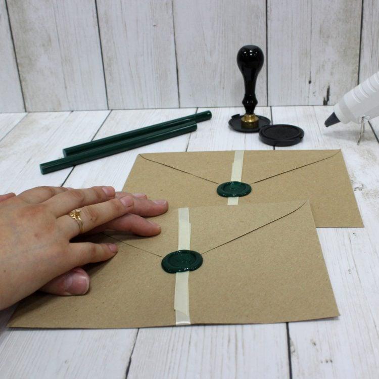 Las manos de una pareja sobre sus invitaciones de boda personalizadas con lacre y las herramientas al fondo