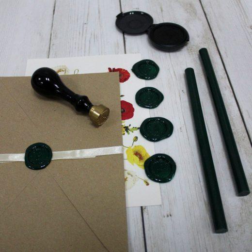El delicado relieve del lacre de cera adorna el sobre de la invitación de boda y las herramientas al lado