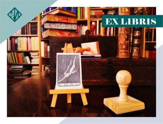 Sello Ex libris personalizado junto a su impresión expuesta en un caballete, en primer plano de una biblioteca